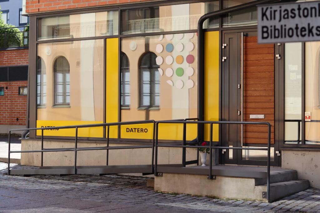 Valokuva Dateron pienryhmätila Studion sisäänkäynnistä Kirjastonkujalla. Oven edessä kaksi porrsta ja toisella puolella ramppi.